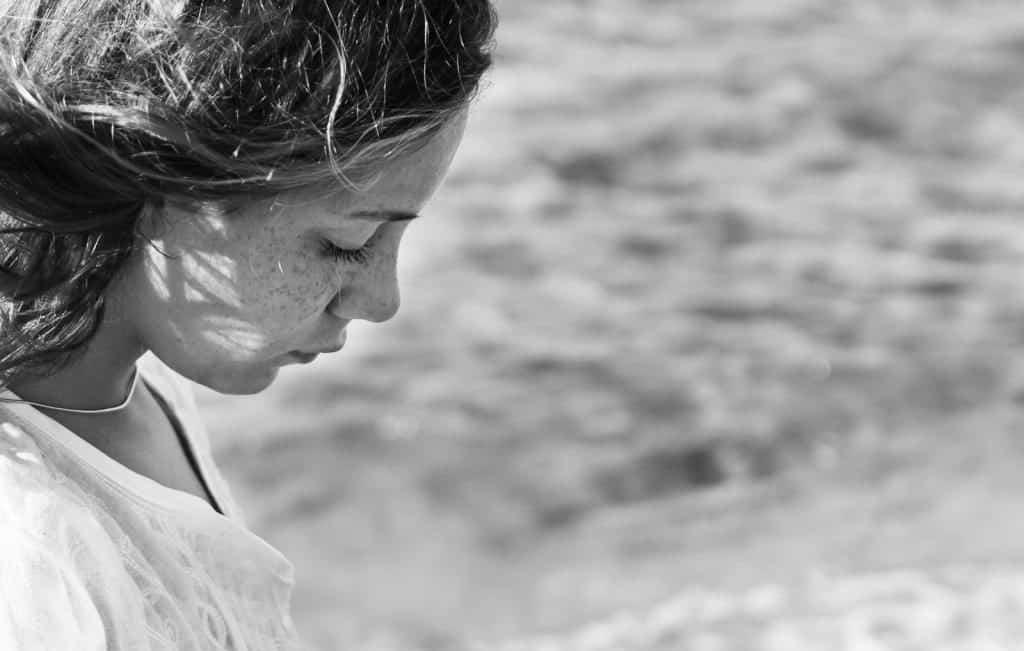 sad young woman staring at beach